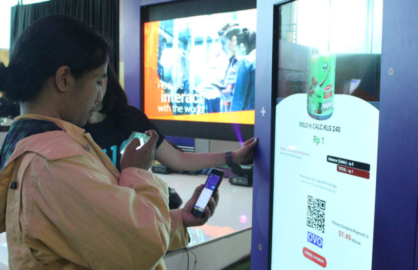 A Woman At A OVO SmartCube Vending Machine In Indonesia