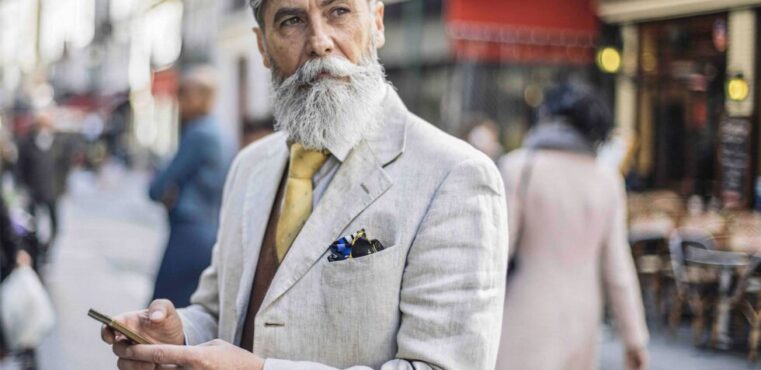 English gentleman with a beard using his smartphone on a busy street.