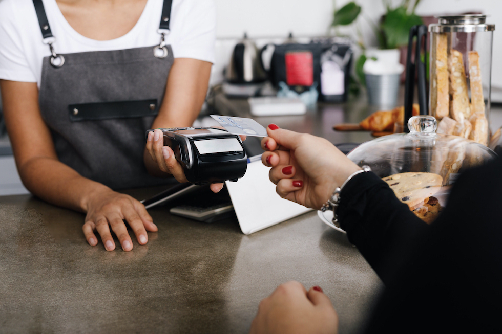A woman using a card reader to process a credit card payment in-store.