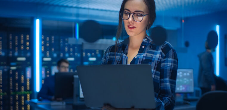 A smart young woman selects fraud management solutions on a laptop with server racks in the background.