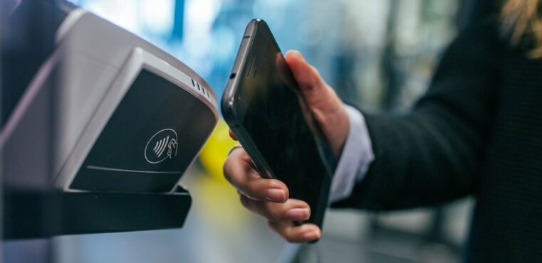 A man uses a phone to make a contactless payment.