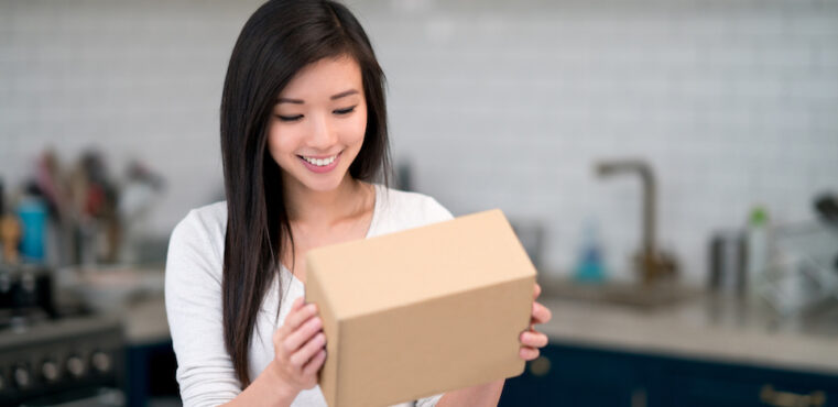 A woman holding a package from an online ecommerce subscription service.