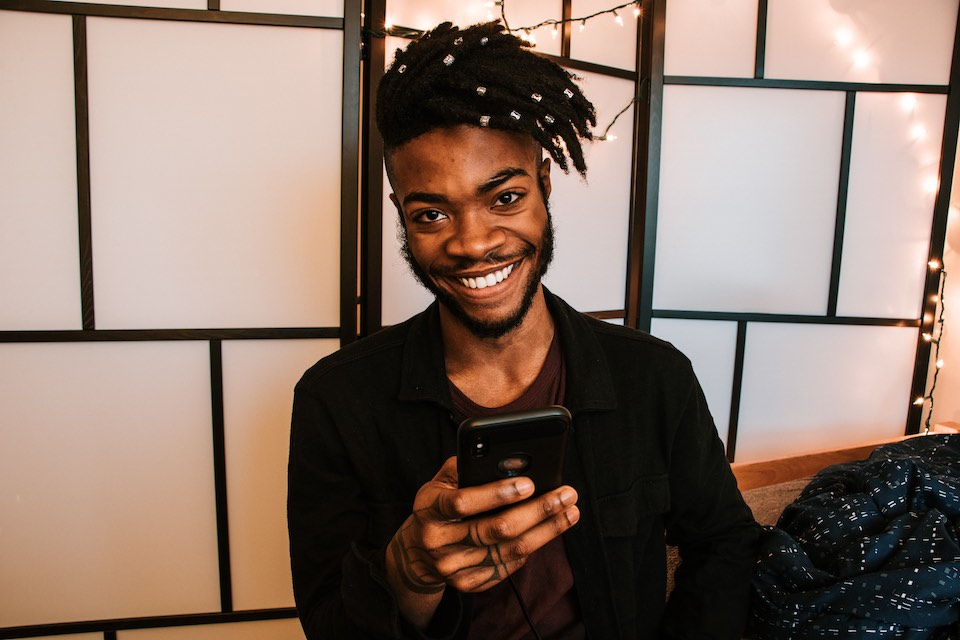 A young man smiles while holding a smartphone and using a wallet payment method.