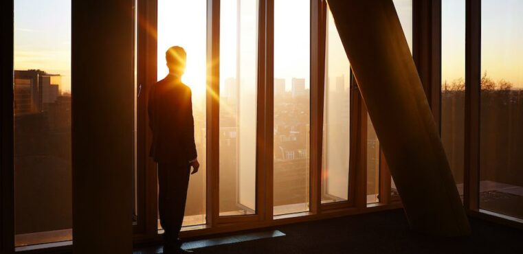 Businessman looks out at city sunrise and contemplates selling his products cross border.