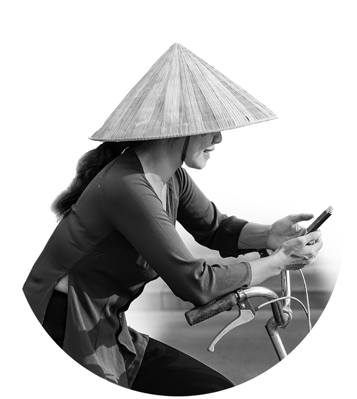A woman rides a bike while making a payment on a phone.