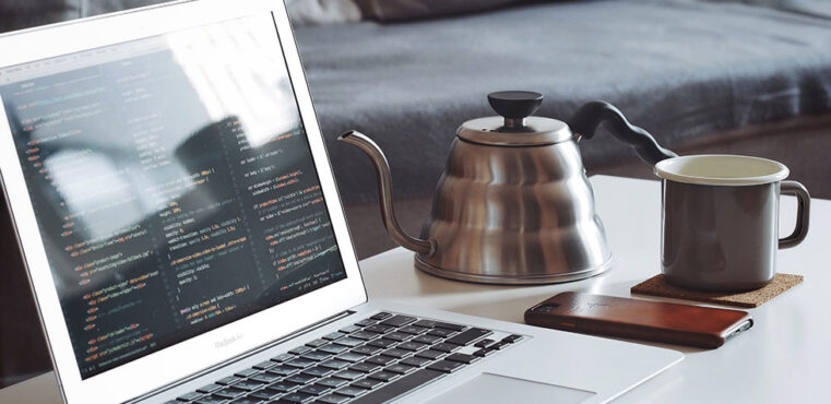 laptop on table with coffee pot and mug