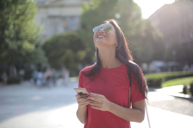 a woman smiles while holding her smartphone