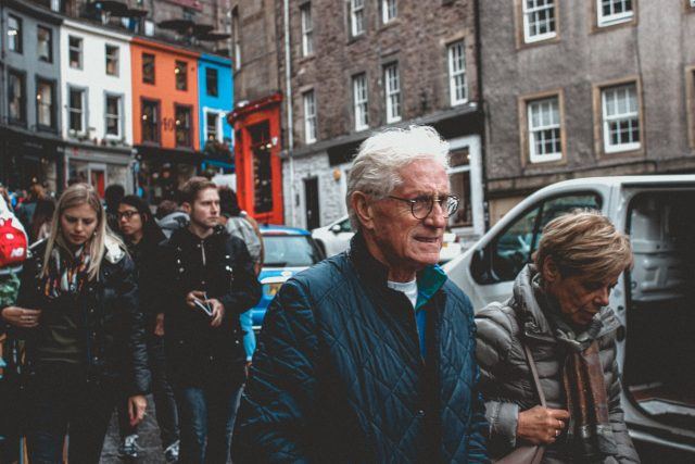 an older couple walk together through a crowded european streeet