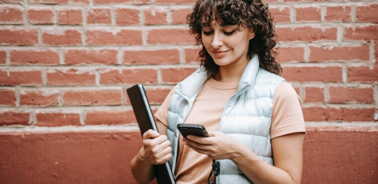woman holds laptop and looks at mobile phone