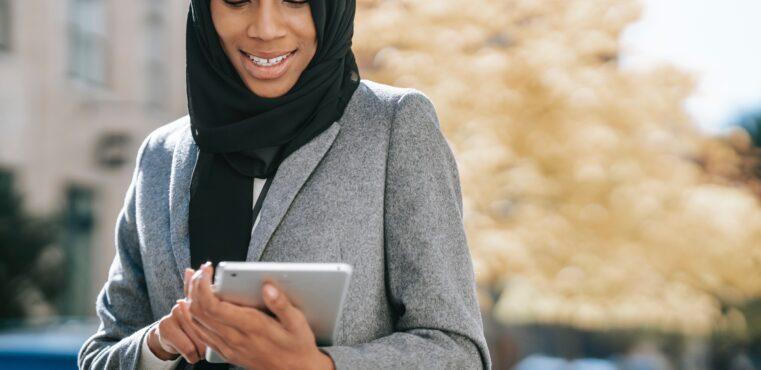 Business woman in hijab uses ipad